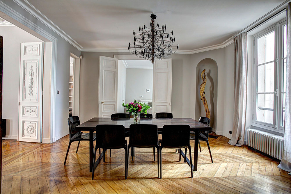 Image of a dining room table and chairs upon a parkay floor with a chandelier above