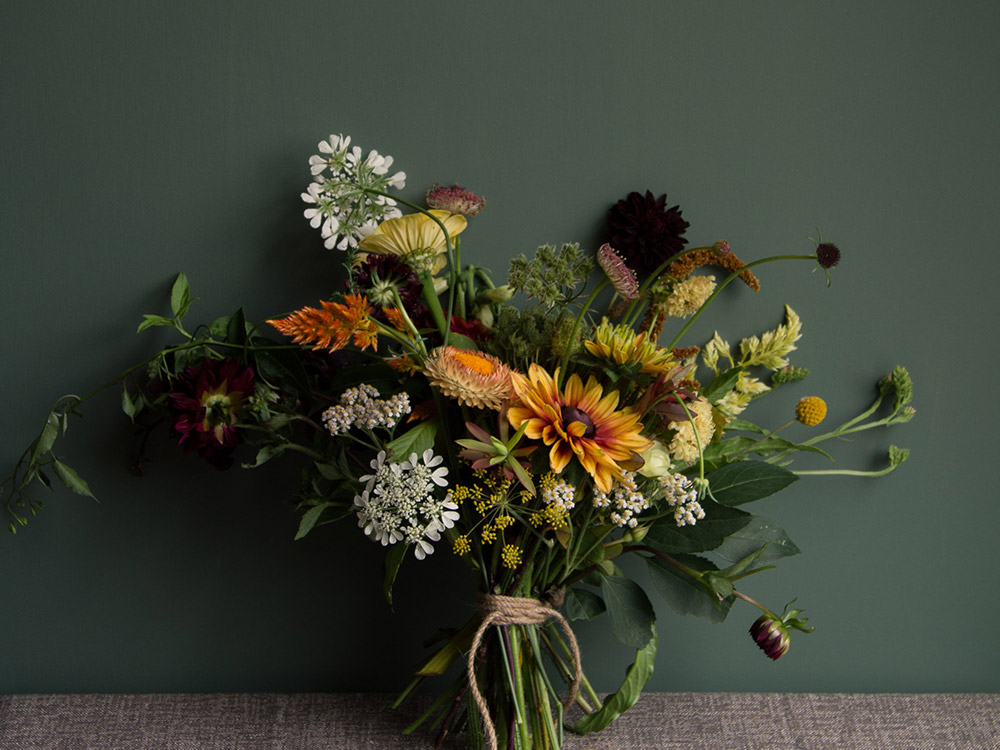 Image of a moody bouquet next to a deep green wall