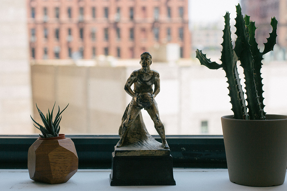 Image of a statue of a young person playing basketball surrounded by cacti