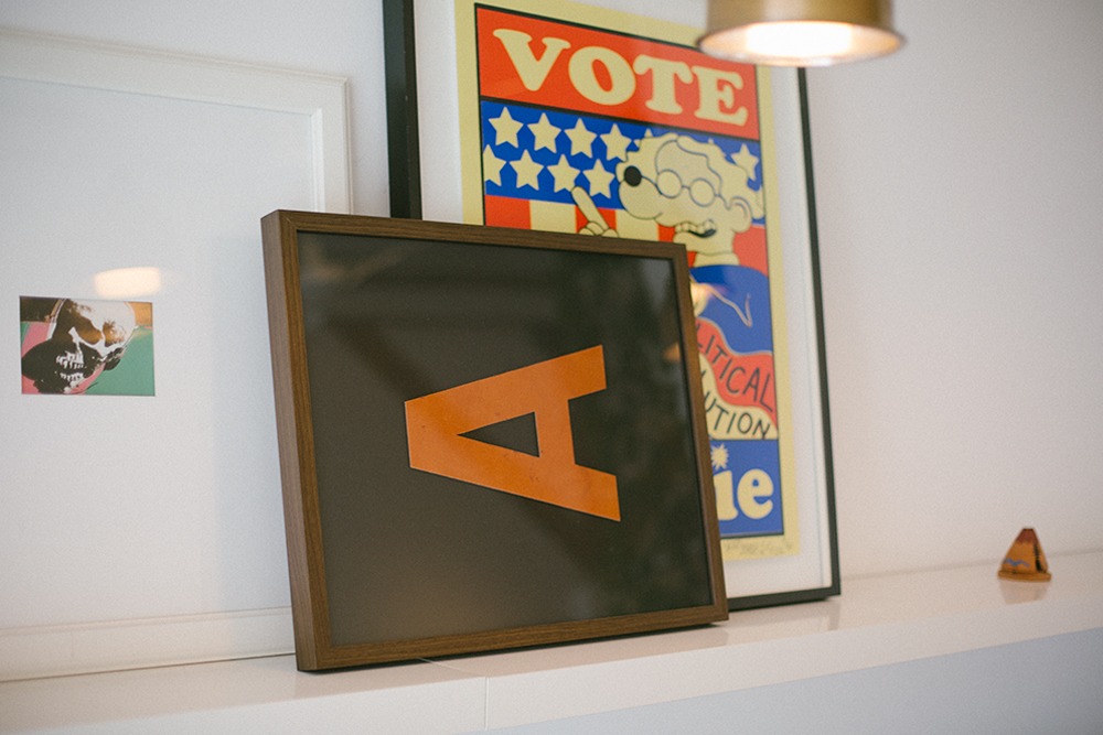 Image of typographic posters in frames leaning on mantel