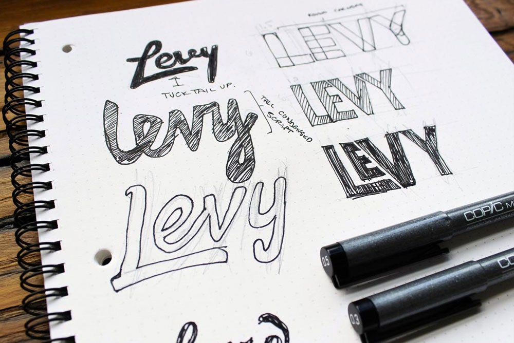 Image of sketchbook of logos for Levy